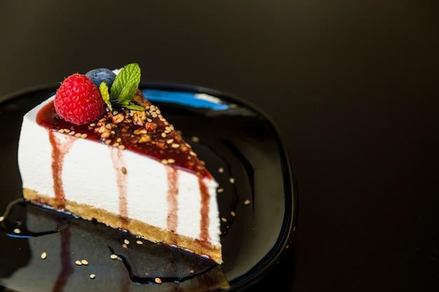 Um cheesecake decorado com framboesa; mirtilo e hortelã na chapa contra fundo preto Foto gratuita