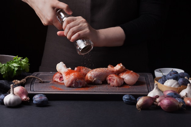 Um chef mulher prepara uma galinha. Foto Premium