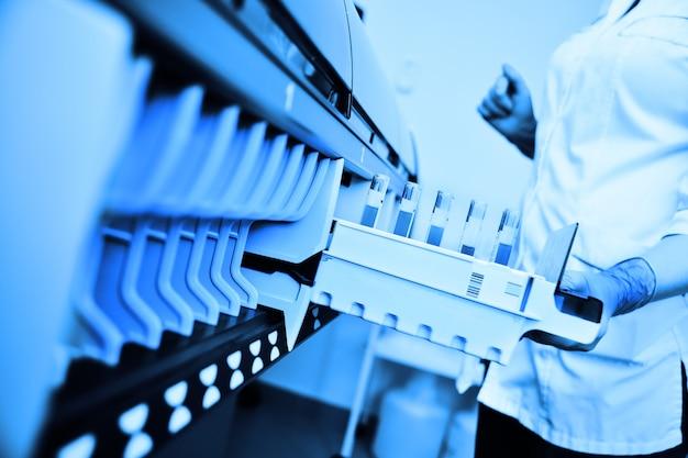Um cientista em um laboratório coloca tubos de ensaio com sangue ou urina no recipiente de um analisador térmico. equipamento médico informatizado moderno Foto Premium