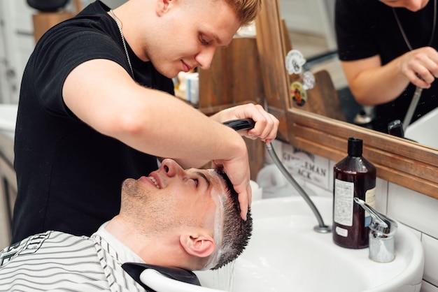 Um cliente do sexo masculino lava o cabelo em uma barbearia Foto Premium