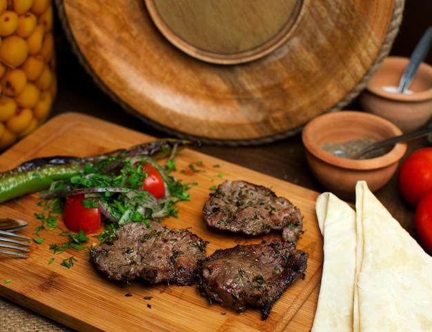 Um close-up frontal vista frito fatias de carne saborosa, juntamente com legumes frescos na mesa de madeira marrom Foto gratuita