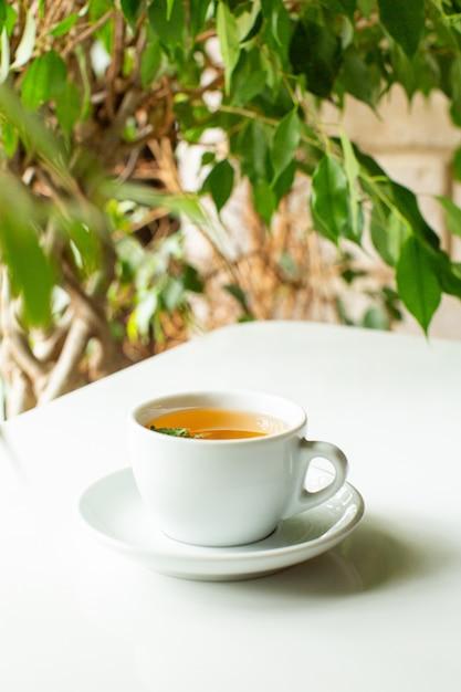 Um close-up vista frontal chá quente dentro de copo branco no chão branco Foto gratuita