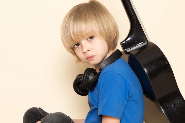 Um close-up vista frontal menino bonitinho na camiseta azul com fones de ouvido pretos, segurando o violão preto Foto gratuita