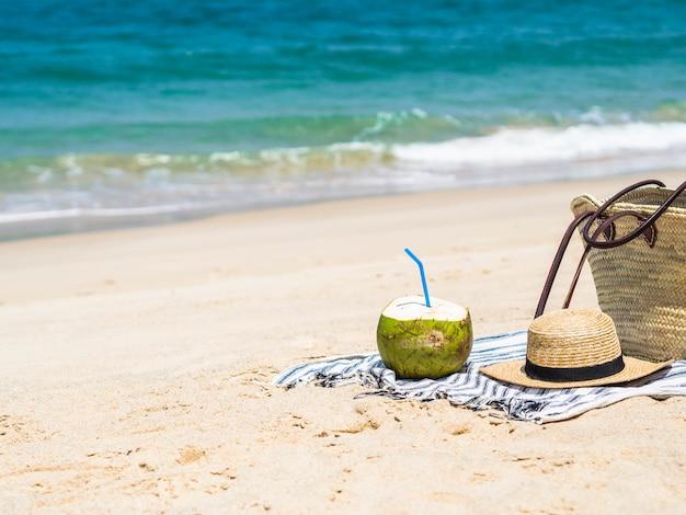 Um coco novo fresco está pronto para comer e um saco da palha e um chapéu de palha das mulheres na toalha em uma praia arenosa contra um mar azul. conceito de viagens de férias tropicais. espaço da cópia Foto Premium