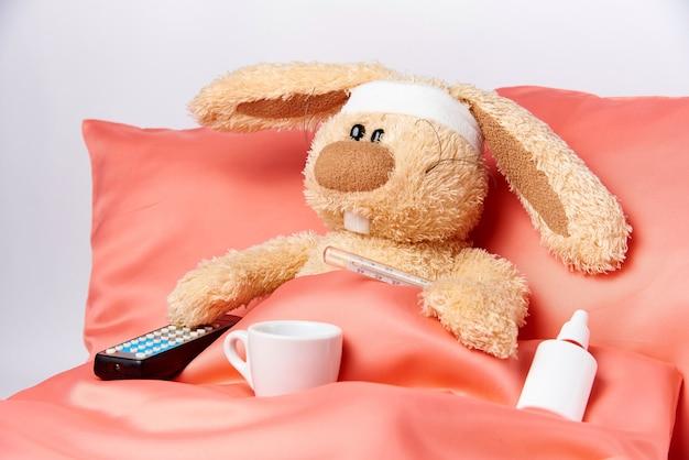 Um coelho insalubre do brinquedo com mediciner e um controle remoto da tevê na cama. Foto Premium