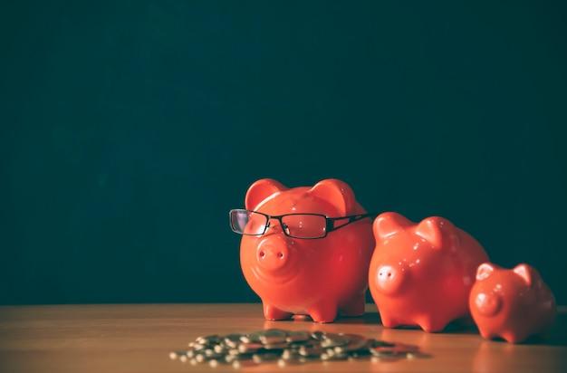 Um cofrinho colocar as moedas de ouro de empilhamento e casa de lousa Foto Premium