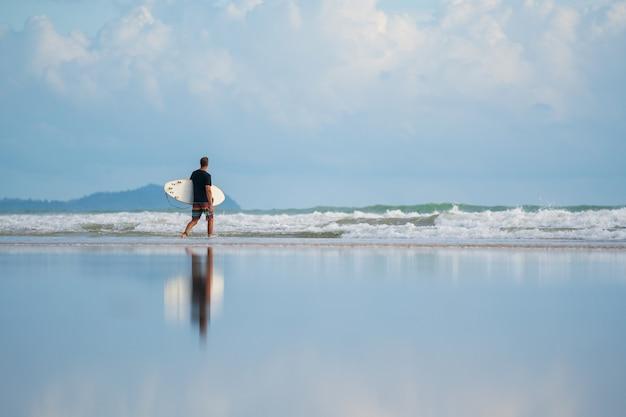 Um com um surf em suas mãos na costa do mar Foto Premium