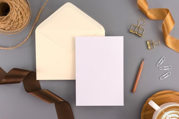 Um conceito de casamento. cartão do convite do casamento no fundo cinzento com fita e decoração. Foto Premium