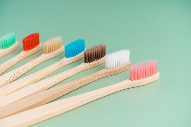 Um conjunto de escovas de dentes antibacterianas ecológicas feitas de madeira de bambu em uma superfície verde clara. tendências de cuidado ambiental. Foto Premium