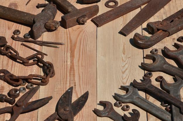 Um conjunto de ferramentas antigas e enferrujadas encontra-se em uma mesa de madeira na oficina Foto Premium