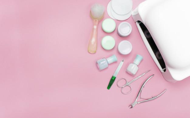 Um conjunto de ferramentas cosméticas para manicure e pedicure em um fundo rosa. esmaltes em gel, limas para unhas e cortadores e a vista superior da lâmpada. composição para cartão com um lugar para texto Foto Premium