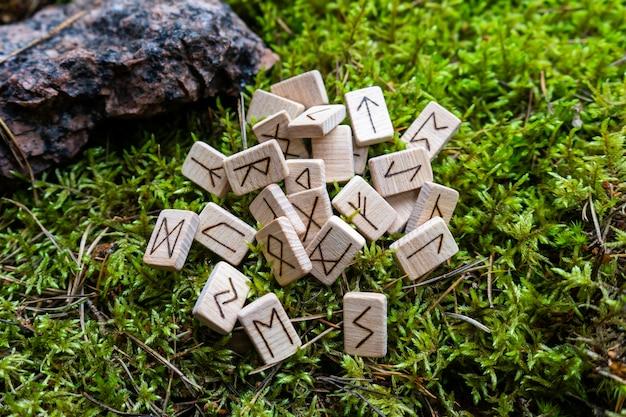 Um conjunto de runas escandinavas feitas em dados de madeira encontra-se em um musgo natural. ferramenta de previsão do futuro, conceito de previsão do futuro. Foto Premium
