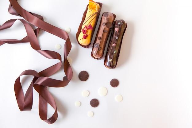 Um conjunto de três eclairs com diferentes recheios e design isolar em uma superfície branca decorada com gotas de chocolate e fita de seda marrom Foto Premium