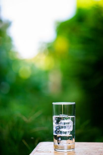 Um copo de água limpa com gelo colocado sobre a mesa, pronta para beber Foto Premium