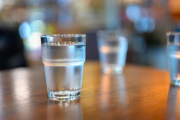 Um copo de água na mesa de madeira pronto para levar para beber. Foto Premium