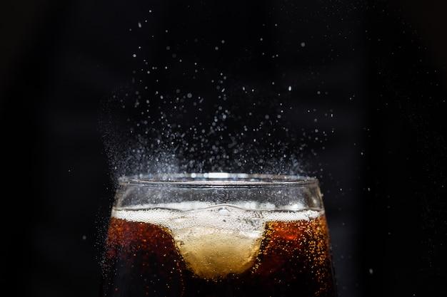 Um copo de bebida cola com sal. em uma parede preta. Foto Premium