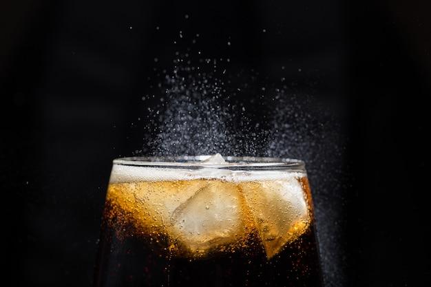 Um copo de bebida de cola com um close-up de sal. Foto Premium