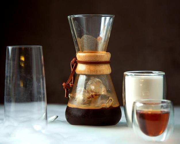 Um copo de café em vidro com formato exclusivo, servido com leite e calda Foto gratuita
