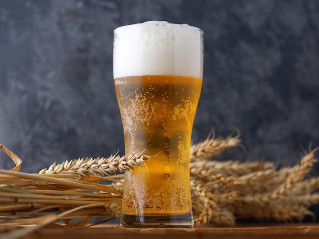 Um copo de cerveja contra uma parede escura Foto Premium