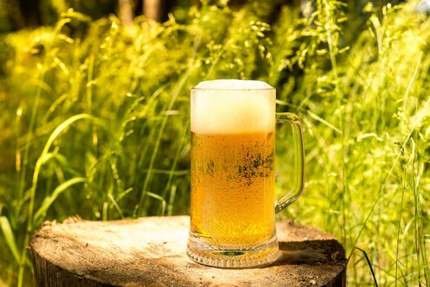 Um copo de cerveja fresca e gelada ao vivo. cerveja na floresta. Foto Premium