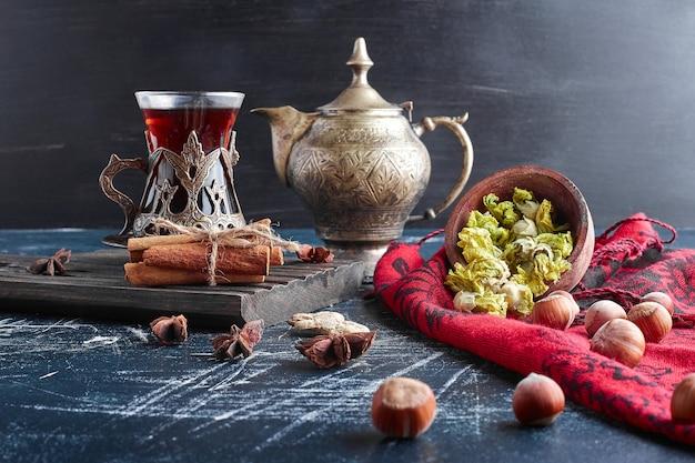 Um copo de chá com especiarias e nozes. Foto gratuita