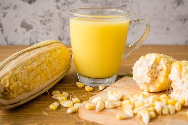 Um copo de leite de milho e milho doce fresco na mesa de madeira. Foto Premium