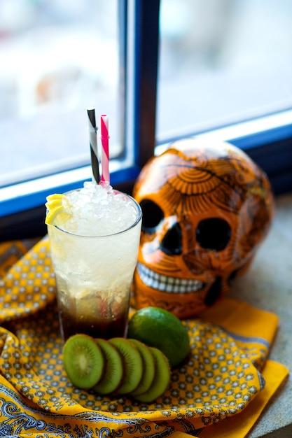 Um copo de limão e kiwis cocktail ao lado do crânio mexicano laranja Foto gratuita
