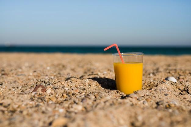 Um copo de suco amarelo com canudo vermelho na areia na praia Foto gratuita