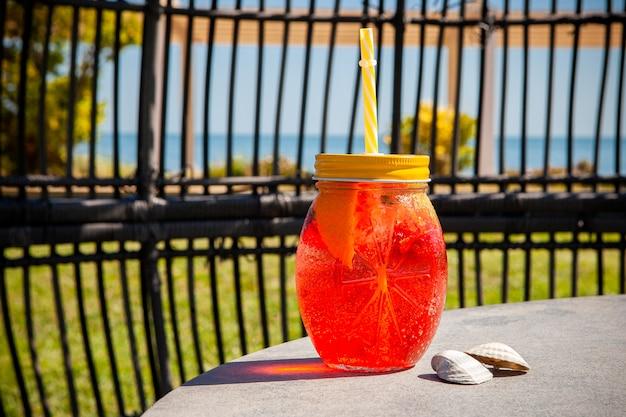 Um copo de suco de frutas vista lateral com o mar Foto gratuita