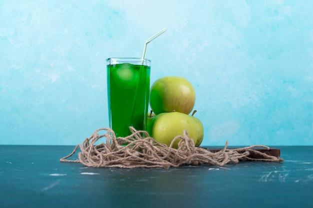 Um copo de suco verde com maçãs em uma bandeja de madeira em azul. Foto gratuita