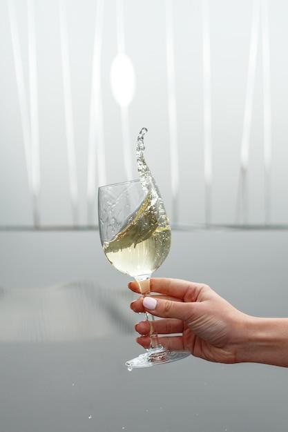 Um copo de vinho branco na mão de uma mulher Foto Premium