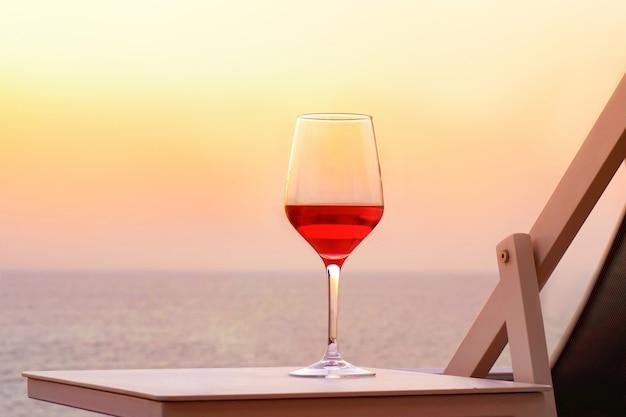 Um copo de vinho tinto em um fundo do mar por do sol. conceito de encontro romântico Foto Premium