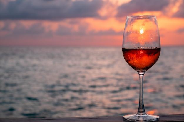 Um copo de vinho tinto no pôr do sol nas maldivas Foto Premium