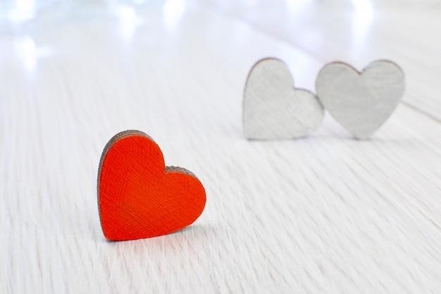 Um coração de madeira vermelho em oposição a dois cinzas em uma luz de madeira. a concepção de amor não correspondido, azarado dia dos namorados Foto Premium
