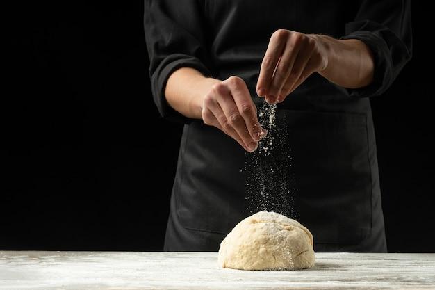 Um cozinheiro chefe em um avental preto em um fundo preto prepara a pizza, o pão ou a massa italiana em um fundo preto. Foto Premium