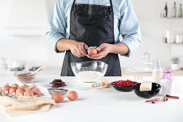 Um cozinheiro em uma cozinha rústica. as mãos masculinas com ingredientes para cozinhar produtos de farinha ou massa, pão, bolos, torta, bolo, pizza Foto gratuita