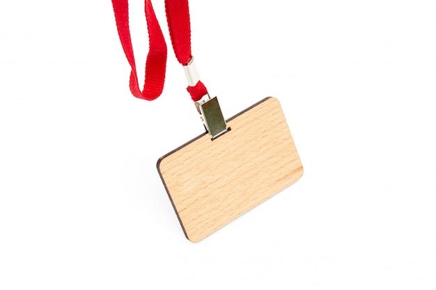 Um crachá de madeira com um campo vazio sob o nome do empregado paira sobre um laço vermelho. isolado Foto Premium