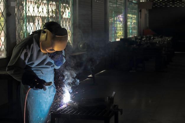 Um craftman está soldando com aço da peça de trabalho. pessoa que trabalha sobre o aço do soldador usando a máquina de soldadura elétrica há linhas de luz que saem e equipamento de segurança na indústria da fábrica. Foto Premium