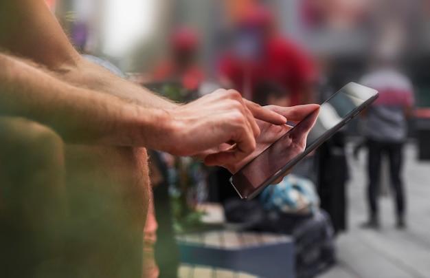 Um dedo de homem tocando uma tela de smartphone Foto gratuita