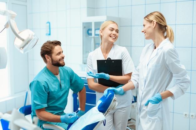 Um dentista e duas enfermeiras estão posando em um consultório odontológico Foto Premium