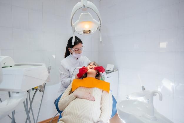 Um dentista profissional trata e examina a cavidade oral de uma mulher grávida em um consultório odontológico moderno. odontologia Foto Premium