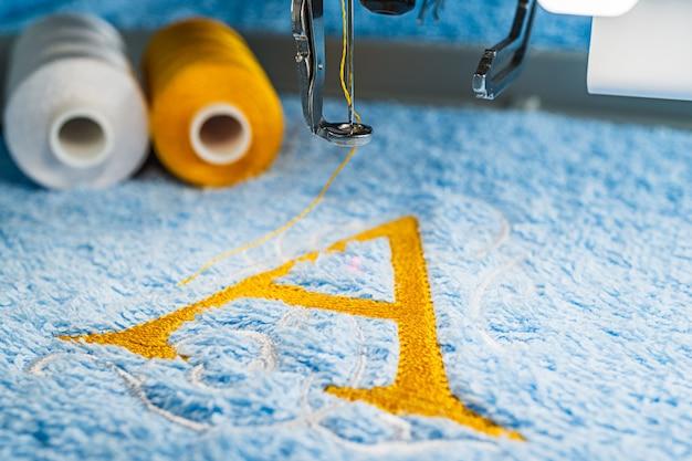 Um design de alfabeto na toalha no aro da máquina de bordar Foto Premium