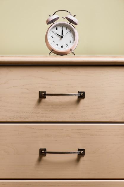 Um despertador em cima do armário de madeira Foto gratuita