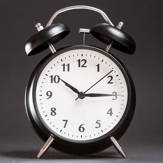 Um despertador no pano de fundo preto Foto gratuita