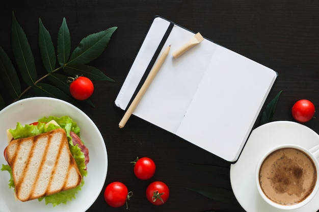 Um diário branco em branco aberto com caneta; tomates; sanduíche e xícara de café sobre fundo preto Foto gratuita
