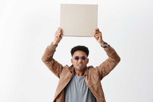 Um em cada dez. eww. retrato de jovem homem de pele escura atraente com penteado afro em roupas casuais e óculos de sol segurando papelão vazio aéreo com expressão de nojo. Foto gratuita