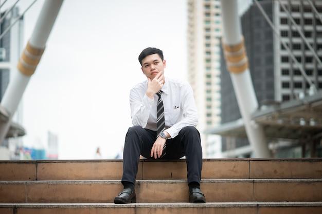 Um empresário de camisa branca está sentado na escada. Foto Premium