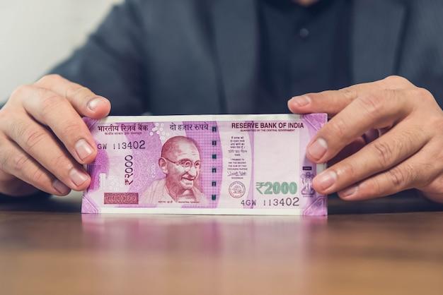 Um empresário de um instituto financeiro contando e exibindo notas de rúpia indiana Foto Premium