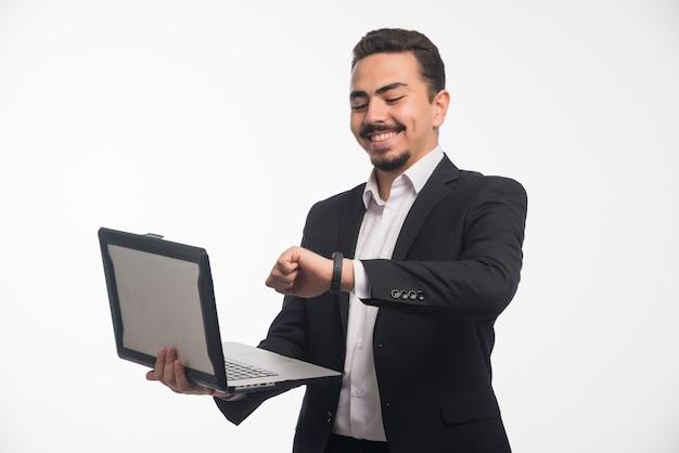 Um empresário em código de vestimenta segurando um laptop e apontando a hora. Foto gratuita