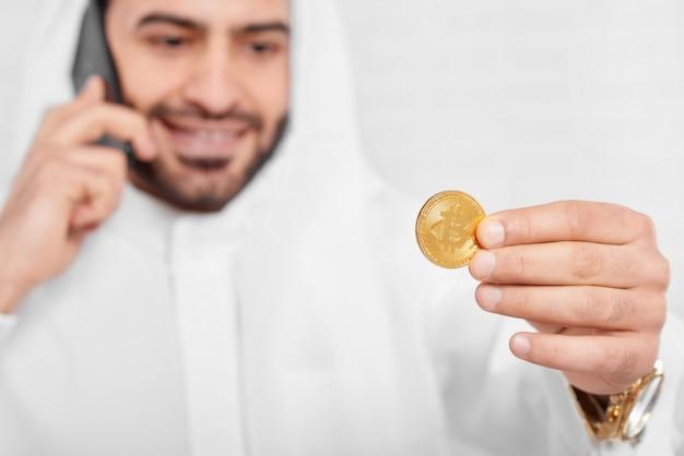 Um empresário muçulmano olha no bitcoin dourado Foto Premium